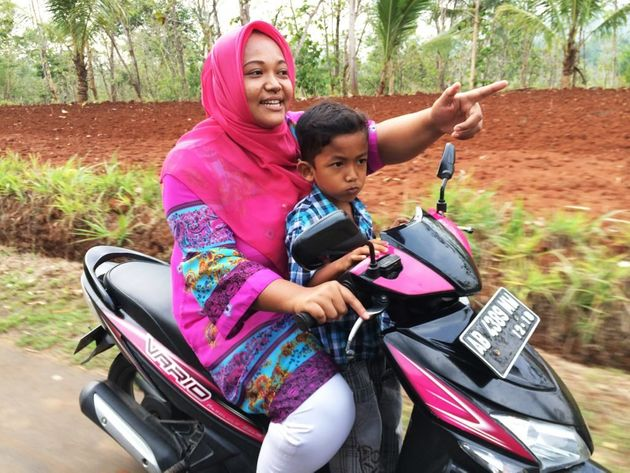 Trisuprapti rides her motorcycle with her son. She says she felt she had nowhere to turn when she got