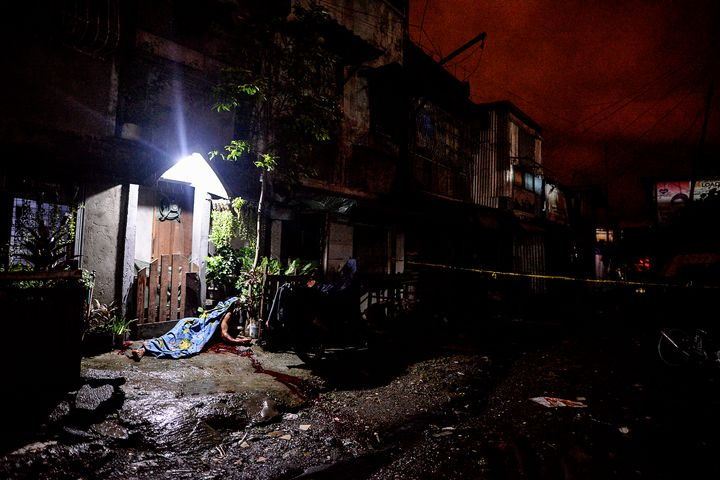 The corpse of a suspected drug pusher lies outside a house after he was shot dead following a police operation at a slum area