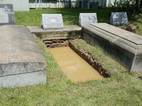 A grave is filled with water in a cemetery in Springfield, Louisiana on Aug. 15, 2016.