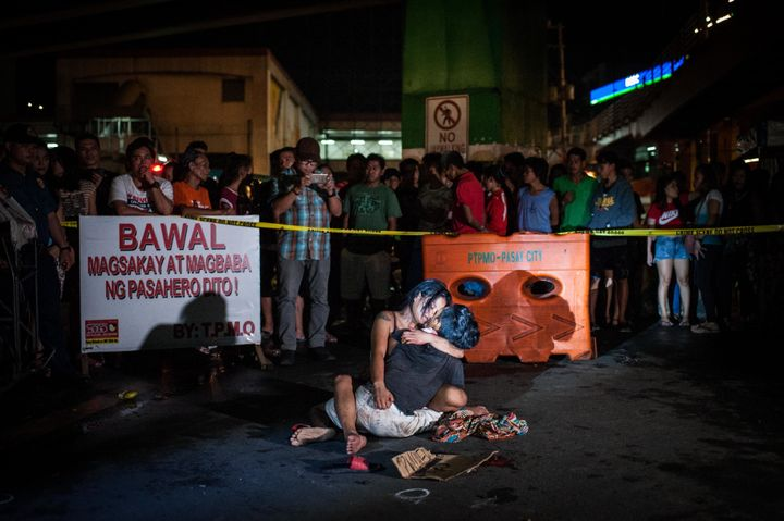 Jennilyn Olayres clutches thebody of her husband, Michael Siaron, after he was shot and killed on a main street in Mani