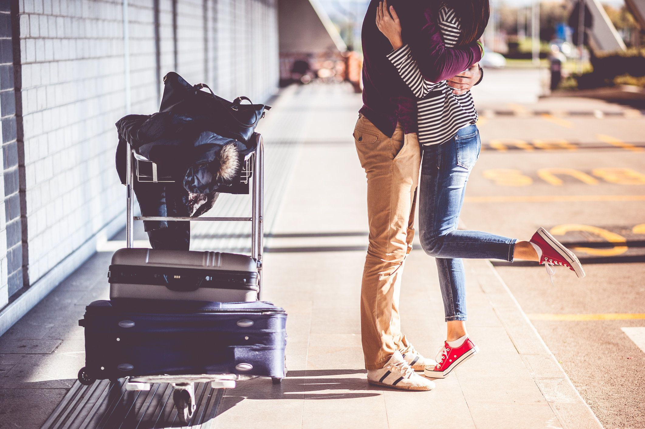 Legs of a young couple that meets outside the airport with suitcase