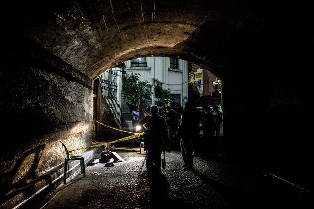 Police and media inspect the corpse of a suspected drug pusher and victim of a vigilante-style execution...
