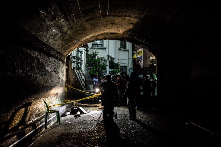 Police and media inspect the corpse of a suspected drug pusher and victim of a vigilante-style execution under a bridge in Ma