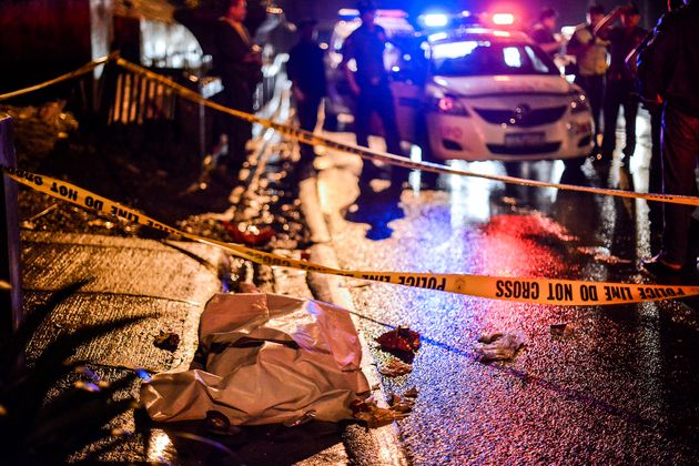 The corpse of a suspected drug pusher and victim of a vigilante-style execution lie along a street in...