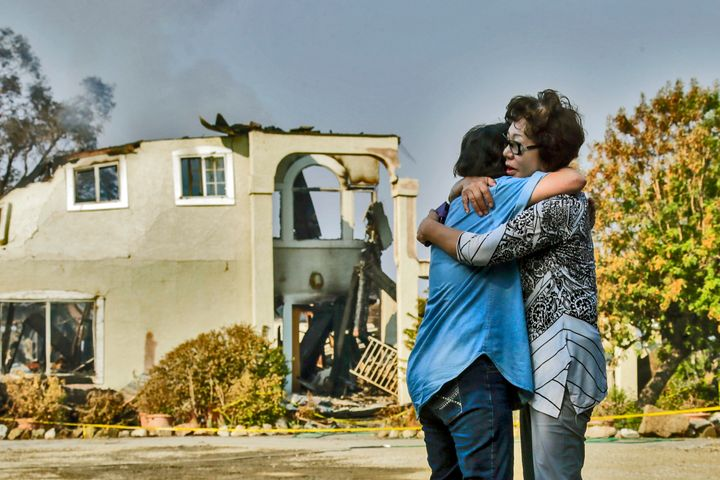 Aurora Harris Heller, 62, left, comforts the owner of a house destroyed in Sand Fire in Santa Clarita, July 26, 201