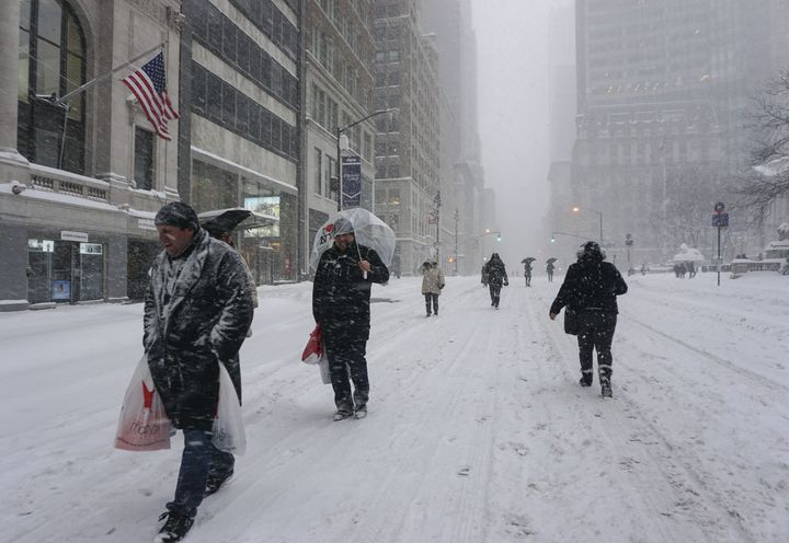 People walk on snow as winter storm Jonas hits New York, Jan. 23, 2016.