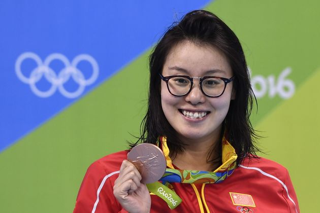 Fu Yuanhui poses with her bronze medal on the podium of the Women's 100m