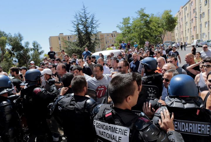 Hundreds walk into the cite des Monts surrounded by policemen in Lupino, Bastia, on the French Mediterranean island of C