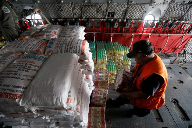 Members of Peru's National Institute of Civil Defense and Peru's Air Force load a cargo plane with aid...