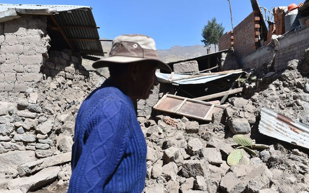 A man walks by toppled houses on August 15, 2016 in the Andean town of Yanque in southern