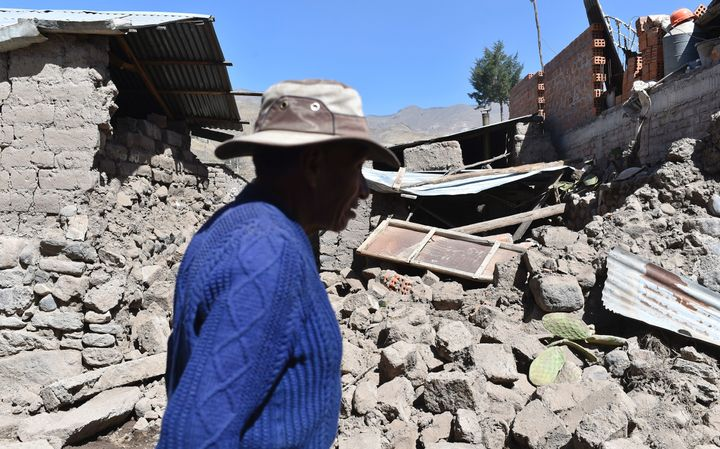 A man walks by toppled houses on August 15, 2016 in the Andean town of Yanque in southern Peru.