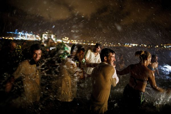 Fishermen and worshippers splash water after take the image of the Virgin of Palm back to the sea during the yearly Virgin of