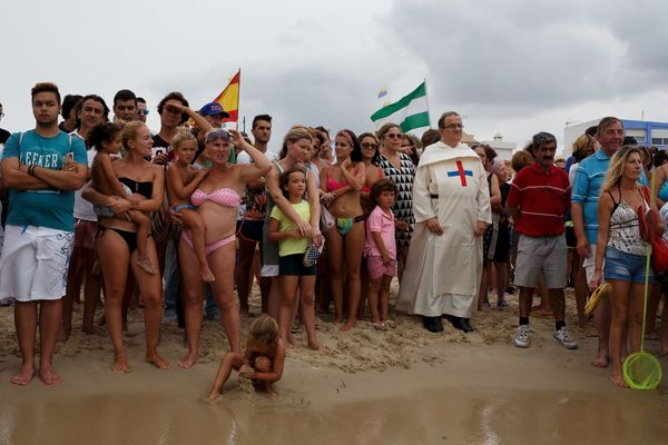 A priest amid worshippers wait for the arrival of the Virgin of Palm on El Rinconcillo beach.