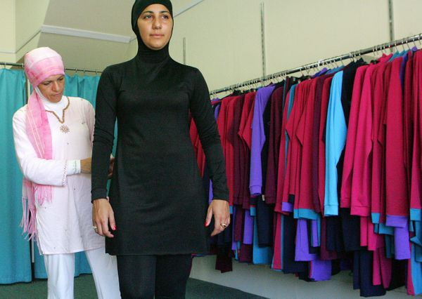 Muslim fashion designer Aheda Zanetti makes adjustments to Australian model Mecca Laalaa's swimsuit.