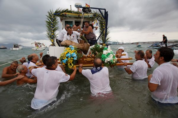Fishermen place the image of the Virgin of Palm on to a wooden base.