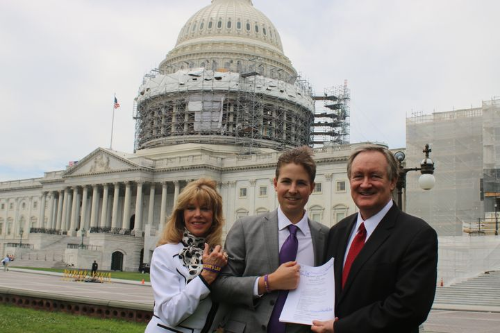 Charlie Smith (Co-Founder of Trevor's Trek Foundation), Trevor Schaefer (Founder of Trevor's Trek Foundation), andSenator Mike Crapo with the signed bill.