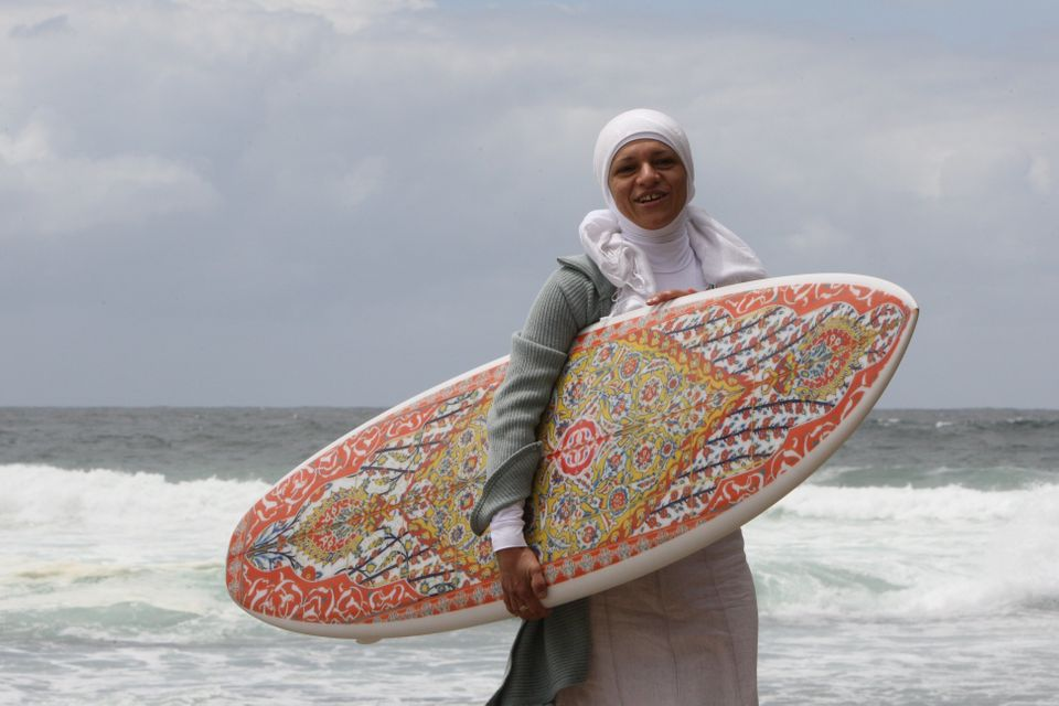 Aheda Zanett, inventor of the burkini swimsuit, poses with a surfboard created by artist Phillip George at Bondi Be