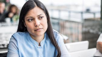 Thoughtful mid adult businesswoman sitting at restaurant