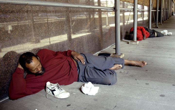 Homeless men sleep on a sidewalk along West 39th street in New York City, July 2, 2004.