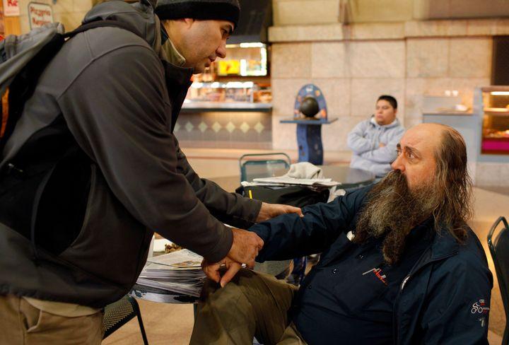 Boston Health Care for the Homeless Program street team member Dr. Patrick Perri examines the sore arm of John Matwichuk, who