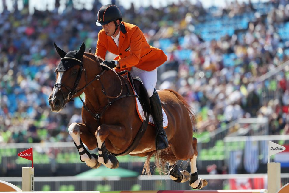 Harrie Smolders of the Netherlands rides Emerald during the jumping individual and team qualifier.