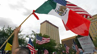 EL PASO, MEXICO:  A man waves a US and a Mexican flags at a demonstration rally during the National Day of Action for Immigrant Justice 10 April 2006 at the Plaza de los Lagartos in El Paso, Texas. Protests, marches and rallies were held across the U.S. today as the issue of immigration rights and justice appears stalled in the U.S. Congress.   AFP PHOTO/ Omar TORRES  (Photo credit should read OMAR TORRES/AFP/Getty Images)