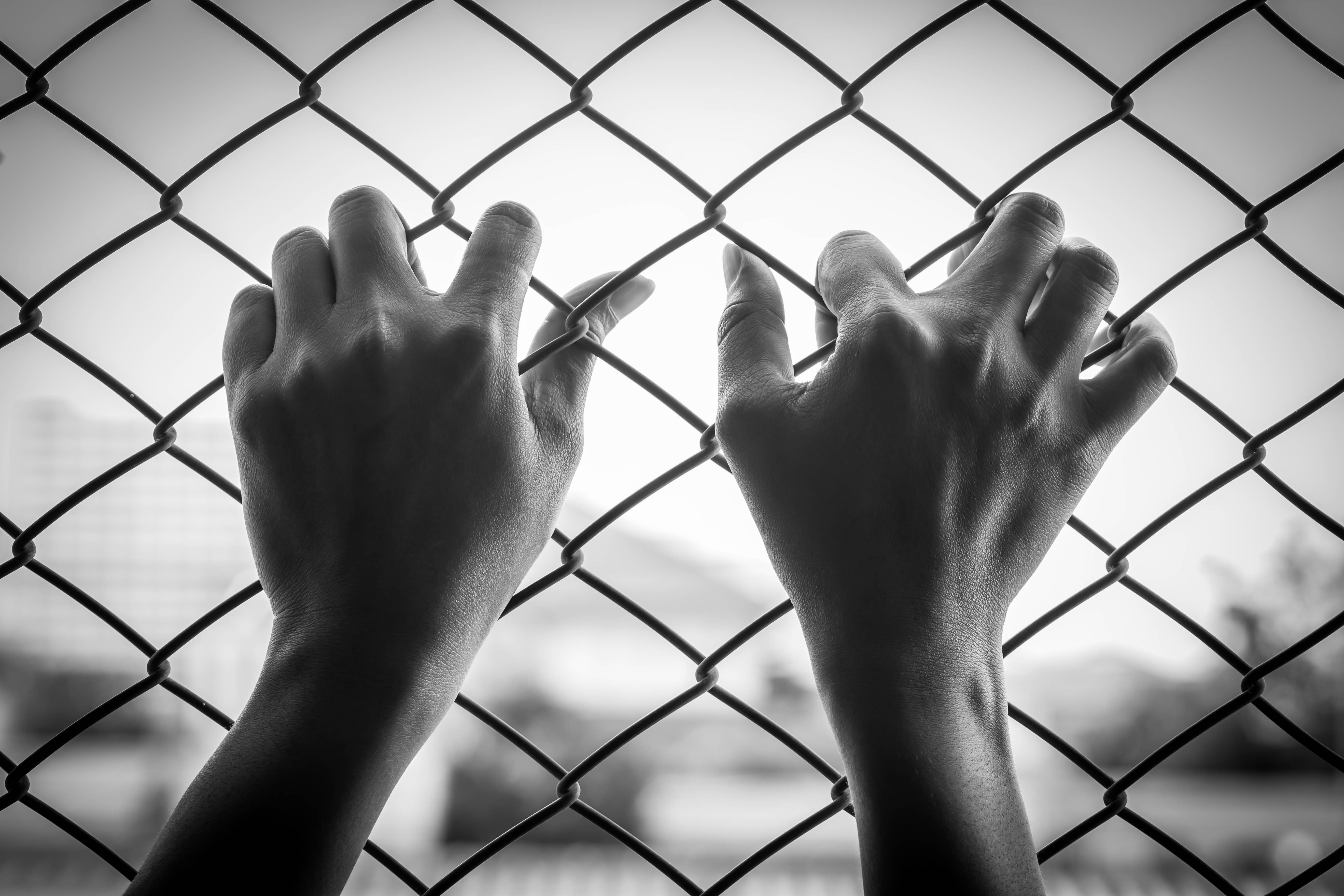 Black and white girl in jail hands close-up, lack of freedom,despair concept.Girl in jail hands close-up, lack of freedom,despair concept.
