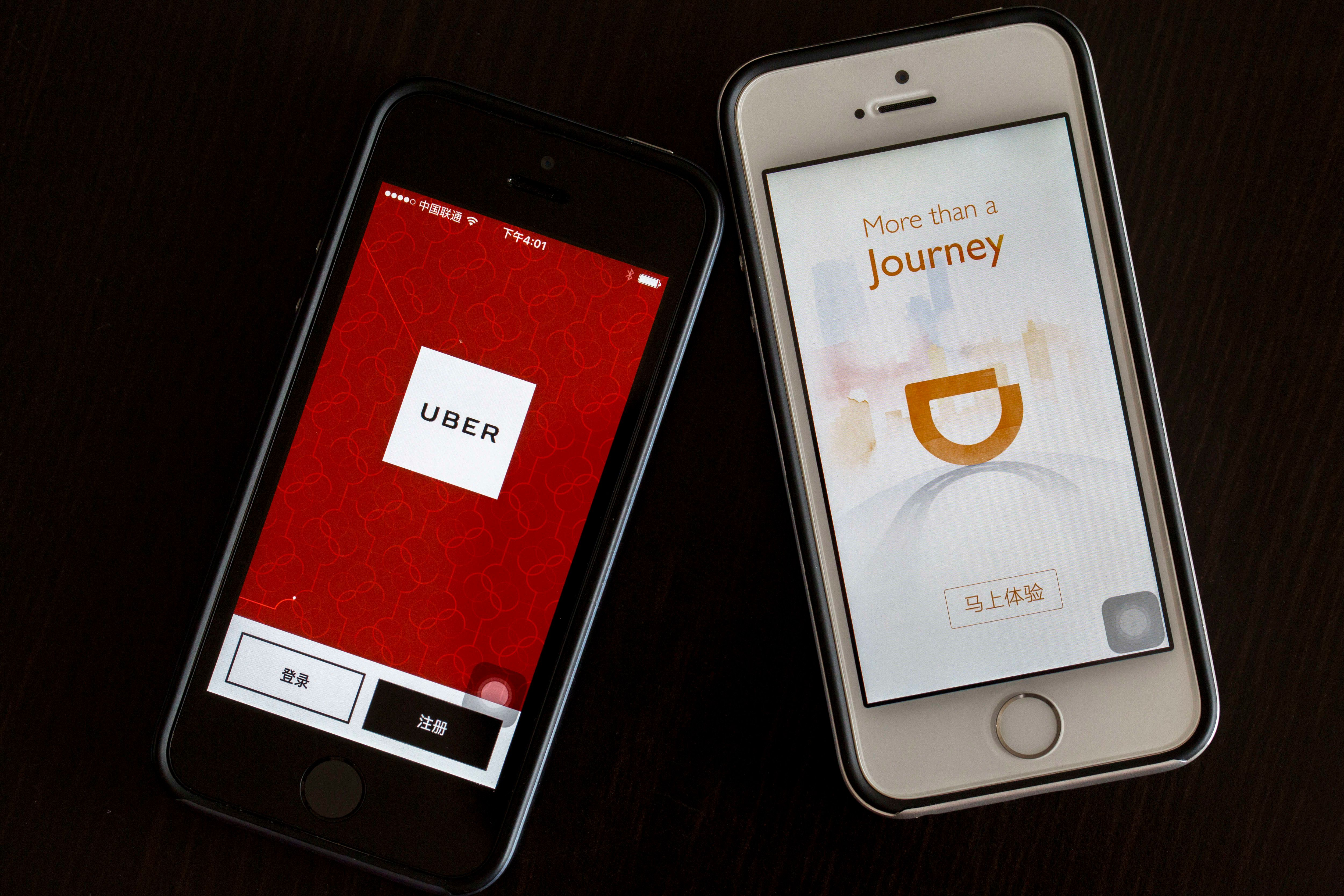 BEIJING, CHINA - 2016/08/02: Apps of Uber and Didi Chuxing on smart phone.  Uber is selling its operation in China to its chief rival, Didi Chuxing, in exchange for a 20 percent stake.  The deal is waiting for the government's approval.  From Nov.1, 2016,  ride-hailing services will be legitimate in China, but those offering rides below cost are prohibited. (Photo by Zhang Peng/LightRocket via Getty Images)