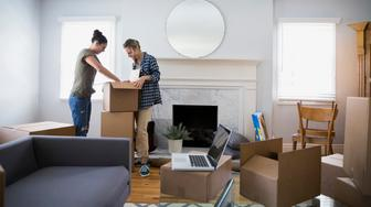 Lesbian couple unpacking moving boxes in living room