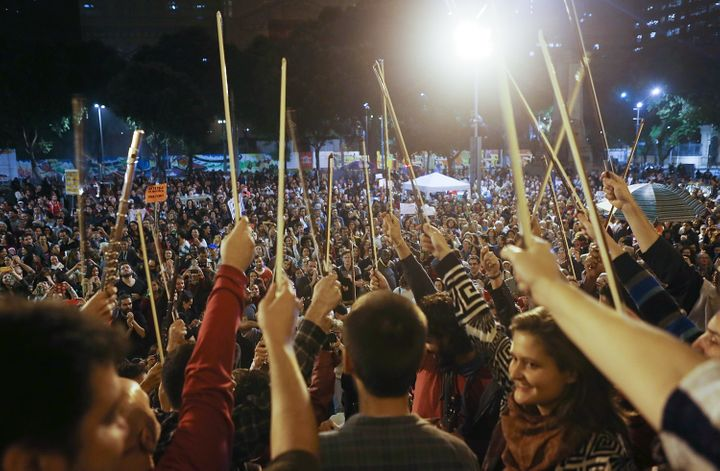 Musicians hold their bows after performing at a rallyprotesting Temer in Rio de Janeiro onJune 10.