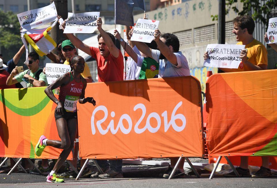 RIO DE JANEIRO, BRAZIL - AUGUST 14:  Kenya's Jemima Jelagat Sumgong runs past protester holding banner against Brazil's inter
