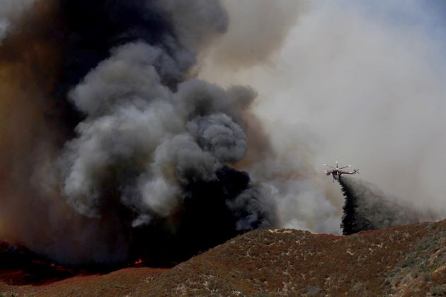 A helicopter battles the Blue Cut fire that broke out late Tuesday morning, August 16, 2016, in the Cajon...