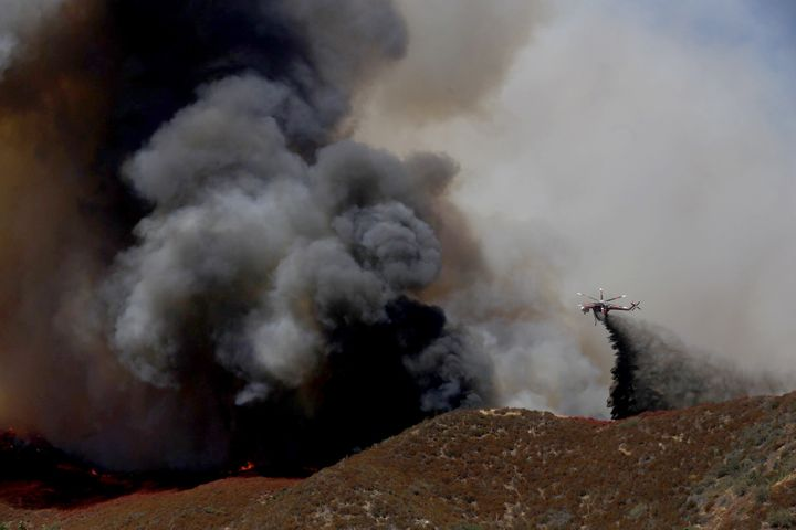 A helicopter battles the Blue Cut fire that broke out late Tuesday morning, August 16, 2016, in the Cajon Pass near Devore ab