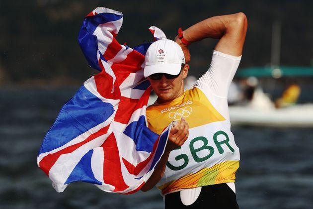 Giles Scott of Great Britain celebrates winning gold in the Finn