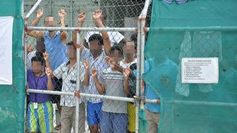 Asylum-seekers look through a fence at the Manus Island detention centre in Papua New Guinea March 21, 2014. Eoin Blackwell/AAP/via Reuters/File Photo ATTENTION EDITORS - FACES PIXELLATED AT SOURCE. THIS PICTURE WAS PROVIDED BY A THIRD PARTY. EDITORIAL USE ONLY. NO RESALES. NO ARCHIVE. AUSTRALIA OUT. NEW ZEALAND OUT.