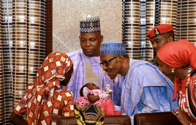 Amina Ali presents her child to Nigerian President Muhammadu Buhari after being