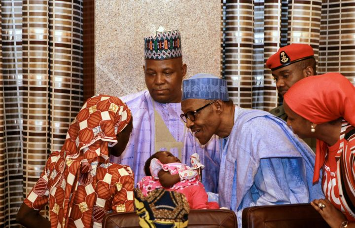Amina Ali presents her child to Nigerian President Muhammadu Buhari after being rescued.