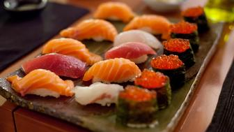 Close-up of sushi plate with salmon in tray on table.