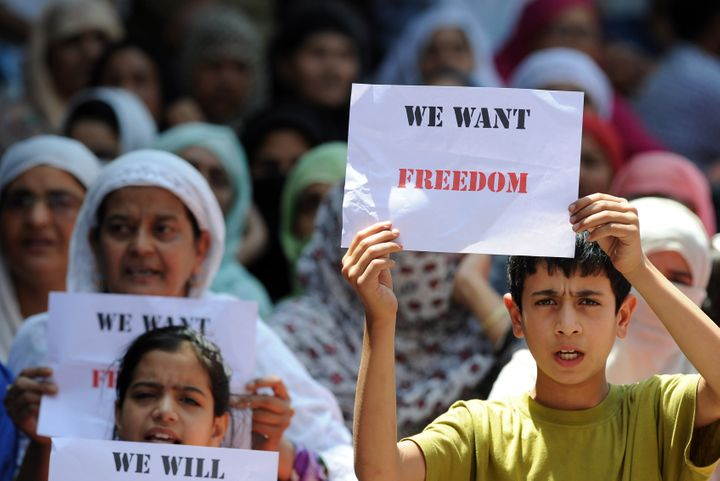 Young Kashmiri protestors hold placards at a protest against civilian killings in Kashmir's ongoing summer unrest, during a c