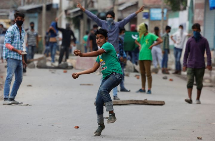 A protester throws stones towards the Indian police during a protest in Srinagar against the recent killings in Kashmir, Augu
