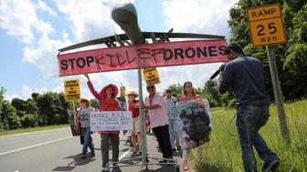 Protesters against drone strikes walk along the highway with a model of a drone in an attempt to deliver a letter to U.S. Central Intelligence Agency as they gather outside CIA headquarters in Langley, Virginia, U.S. on June 29, 2013. REUTERS/Jonathan Ernst/File Photo