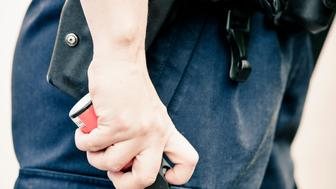 Midsection of a police officer holding pepper spray