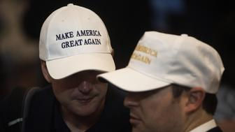 Attendees wear hats reading 'Make America Great Again' during a goodbye reception with Donald Trump, 2016 Republican presidential nominee, not pictured at the Westin Hotel in Cleveland, Ohio, U.S., on Friday, July 22, 2016. A day after accepting the Republican presidential nomination in a speech that signaled a more serious turn heading into the general election, Trump ripped into former primary competitor Ted Cruz, revisiting their ugly feud over Cruzs wife and father. Photographer: Ty Wright/Bloomberg via Getty Images