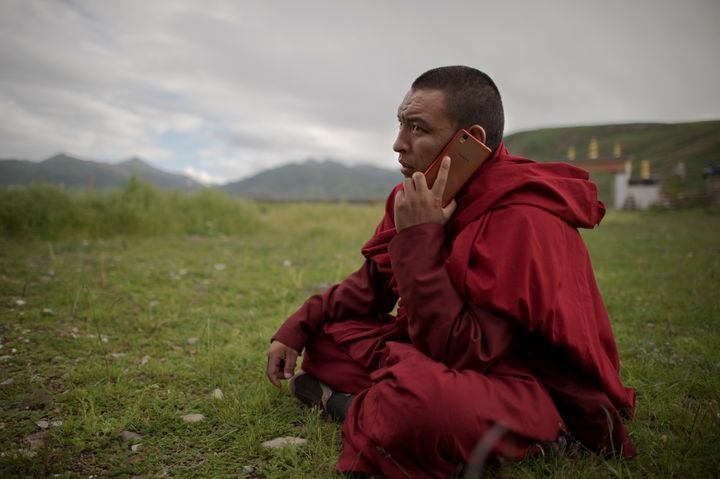 A Tibetan Buddhist monk talks on his smartphone as he sits on the grassland of the Tibetan Plateau in Yushu County.