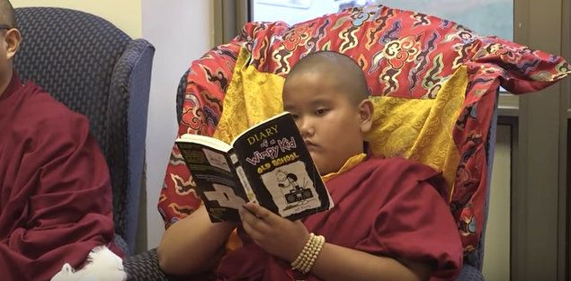 """Jalue Dorje reads """"Diary of a Wimpy Kid"""" during a Tibetan Buddhist ceremony."""