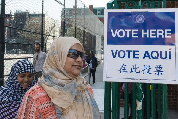 Two women walk past a voting sign at PS 3 on April 19, 2016 in the Brooklyn borough of New York City.
