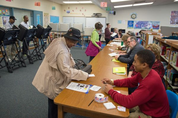 A woman is checked in to receive her ballot during Missouri primary voting at the Griffith Elementary School on March 15, 201