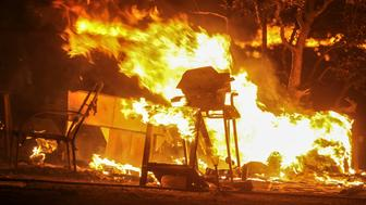 A barbecue and other items burn as the the Blue Cut wildfire rages near Cajon Pass, north of San Bernardino, California, on August 16, 2016.   A rapidly spreading fire raging east of Los Angeles forced the evacuation of more than 82,000 people on August 16 as the governor of California declared a state of emergency. Despite the efforts of 1,250 firefighters with more on the way, none of the inferno was contained as of late on August 16 , state firefighting agency Cal Fire spokeswoman Lynne Tolmachoff told AFP. The wildfire poses 'imminent threat to public safety, rail traffic and structures,' according to the website, which said 82,640 people fell under an evacuation warning. / AFP / RINGO CHIU        (Photo credit should read RINGO CHIU/AFP/Getty Images)