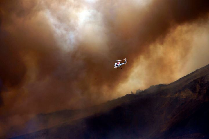 A firefighting helicopter maneuvers around power lines and smoke to make a water drop during the Blue Cut fire at the Cajon P