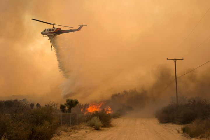 A helicopter makes a water drop at the Blue Cut wildfire in Phelan,California.